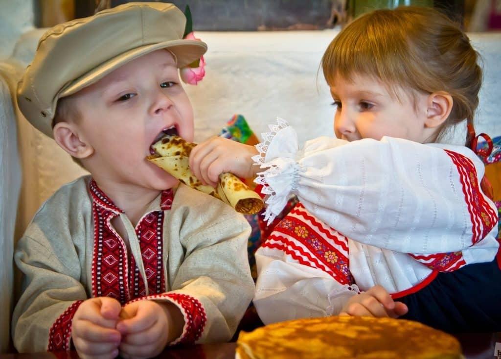 Children feeding each other a Russian blini