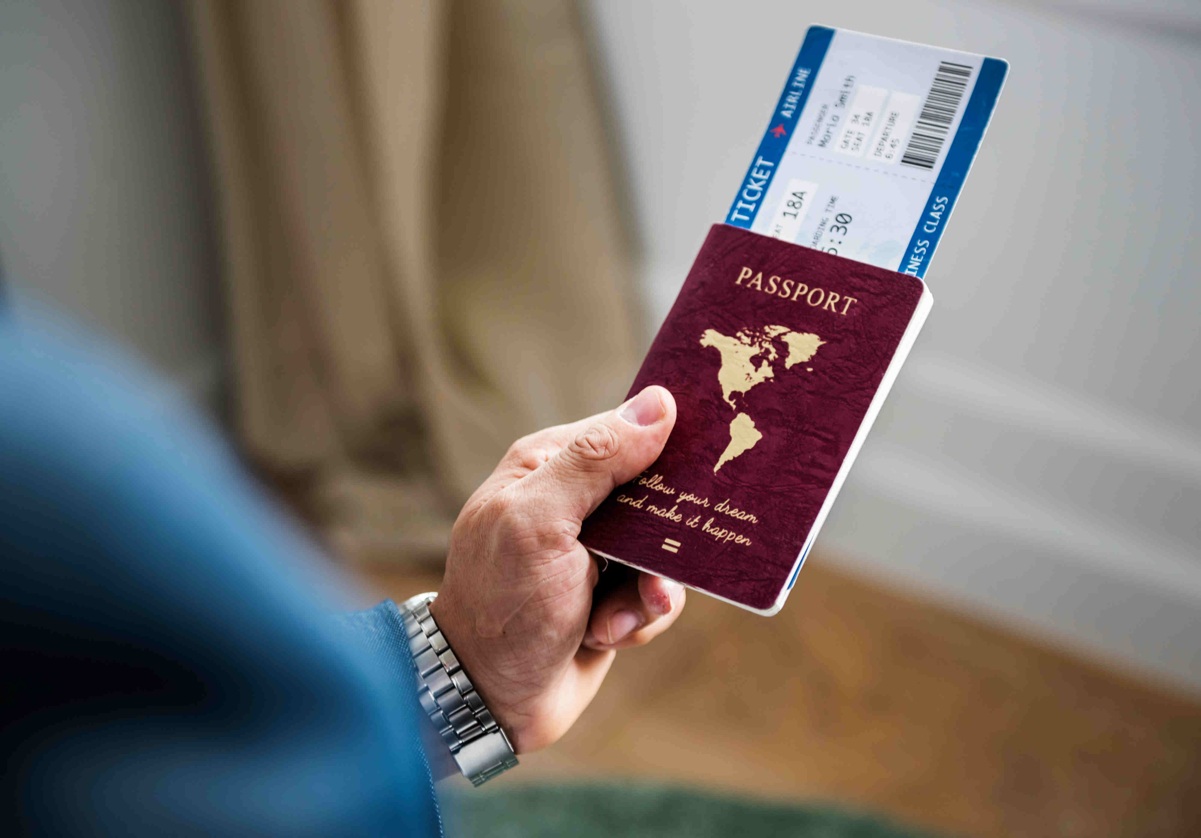 Passport in a man's hand with a boarding pass sticking out